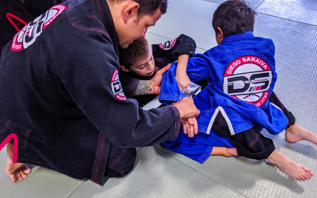 Instructor Diego instructing kids attempting to do a kimura arm lock